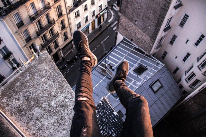 Nogi mężczyzny siedzącego na dachu wieżowca
